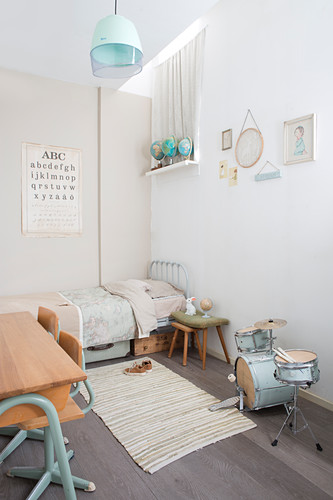 Small drum kit and vintage-style accessories in child's bedroom