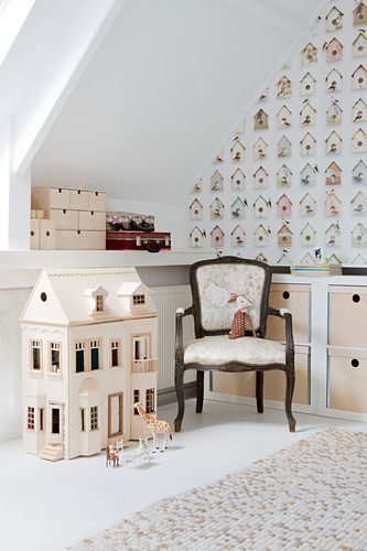 Dolls' house and Baroque chair in room with sloping ceiling and wallpaper with pattern of bird nesting boxes