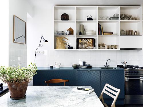 Wohnküche mit dunkelblauer Küchenzeile und offenen Regalen