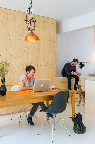 Woman working on laptop on dining table and man sitting on kitchen worksurface