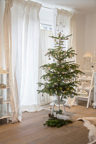 Christmas tree on stool next to window with airy white curtains