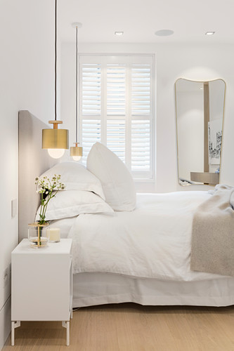 Golden pendant lamps flanking bed in white bedroom