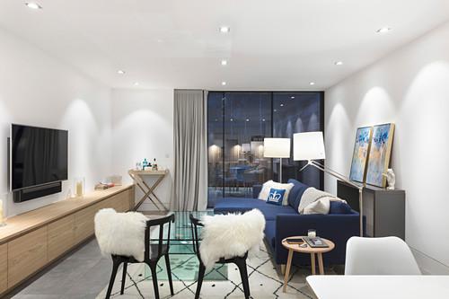 Modern, brightly lit living room at twilight