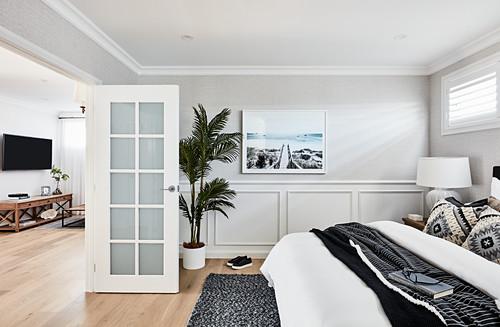 Großes Doppelbett in hellem Schlafzimmer mit Kassettenverkleidung im Sockelbereich, offene Tür