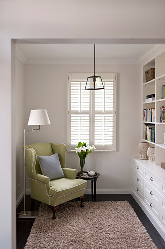 Lime-green wing-back chair, standard lamp and side table opposite fitted bookcases in living room
