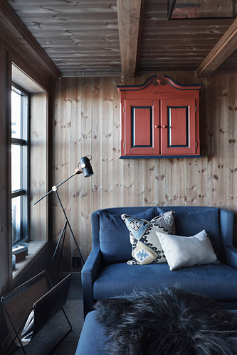 Blue sofa against wooden wall in cosy seating area of cottage