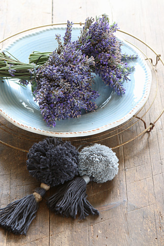 Posies of lavender on plate next to two pompoms with tassels