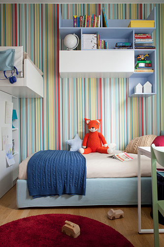 Bed below wall-mounted shelves on multicoloured striped wallpaper in sibling's bedroom