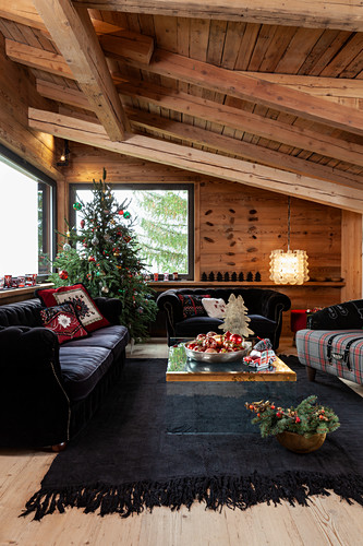 Black sofa set and decorated Christmas tree in living room of chalet