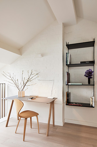 Desk and chair against whitewashed brick wall and black wall-mounted shelves