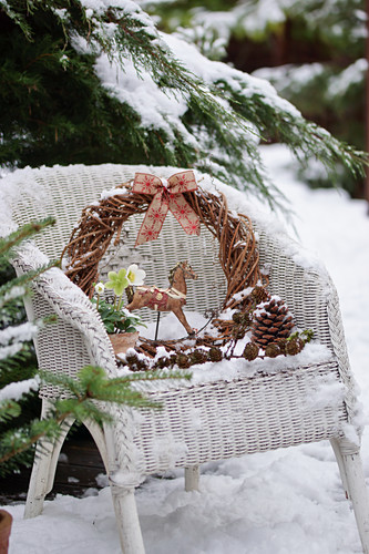 Kleines Weihnachts-Arrangement auf Korbsessel im Schnee