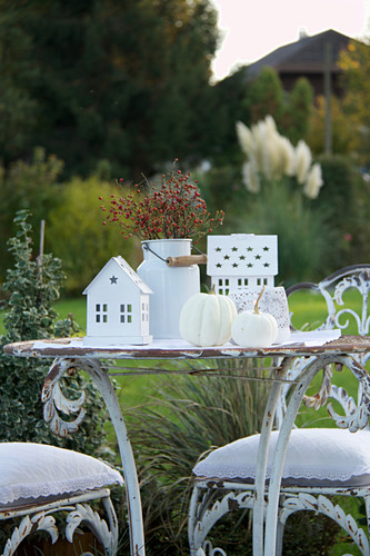 White, shabby-chic seating area in garden with autumnal decorations