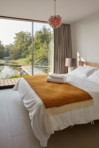 Bedroom with glass wall overlooking lake jetty