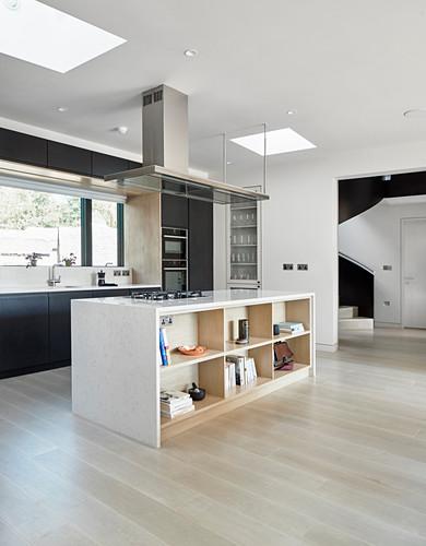 Island counter with shelves below in open-plan minimalist kitchen