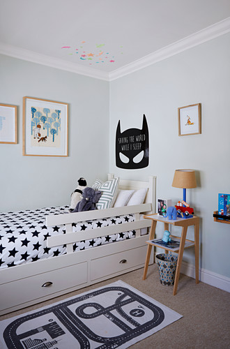 Batman motif above child's bed with black-and-white, star-patterned bed linen