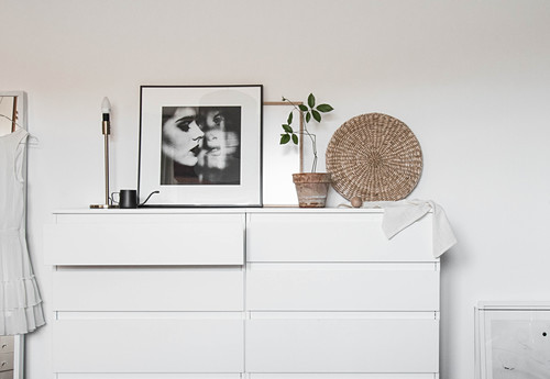 Black-and-whit photo, table lamp and houseplant on white chest of drawers