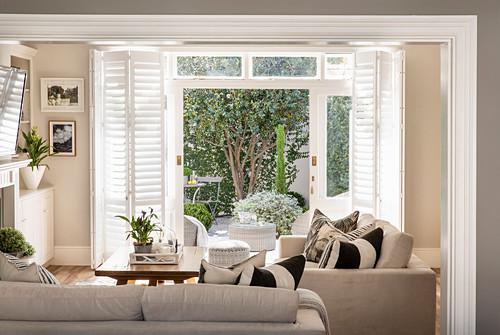 Wohnzimmer in Beige mit Blick auf die sonnige Terrasse