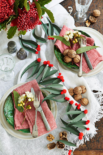 A table laid for Christmas decorated with a leaf pompom garland