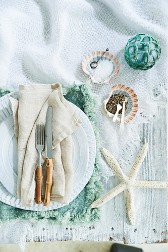 Maritime table decoration with starfish, fishing ball and shells