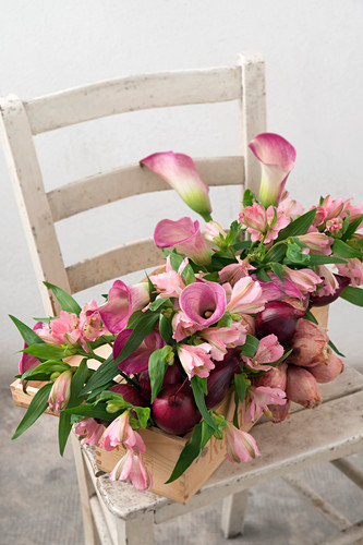 Handmade flower arrangement of Peruvian lilies, calla lilies and red onions in wine box