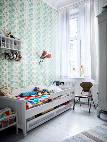 Wooden bed and patterned wallpaper in child's bedroom