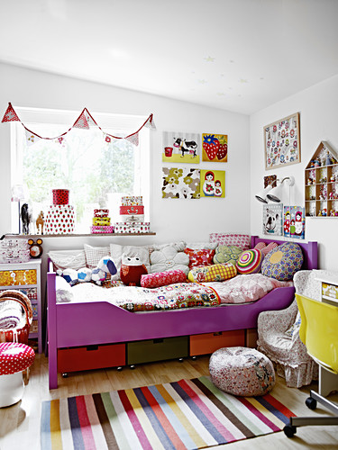Scatter cushions and quilt on child's bed, bunting above window and decorations on walls in girl's bedroom