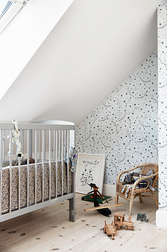 Cot below sloping ceiling in attic nursery with star-patterned wallpaper