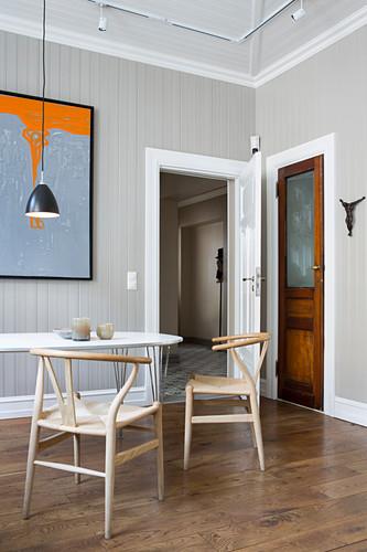 Designerstühle am Tisch im Esszimmer mit grauer Wandverkleidung
