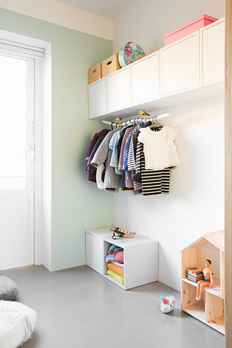 Wall-mounted cupboards and clothes rail in simple child's bedroom