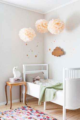 Pompoms above extendable child's bed in bedroom
