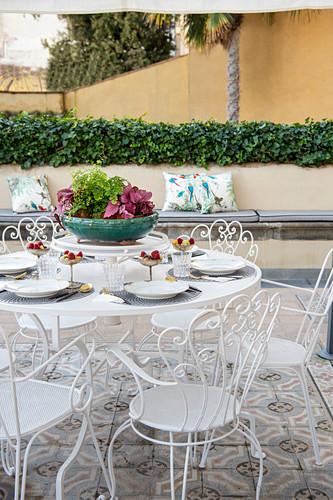 Gedeckter Terrassentisch mit weißen verschnörkelten Metallstühlen