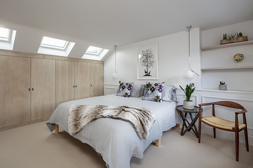 White bedroom with beige fitted wardrobes below sloping ceiling with skylights