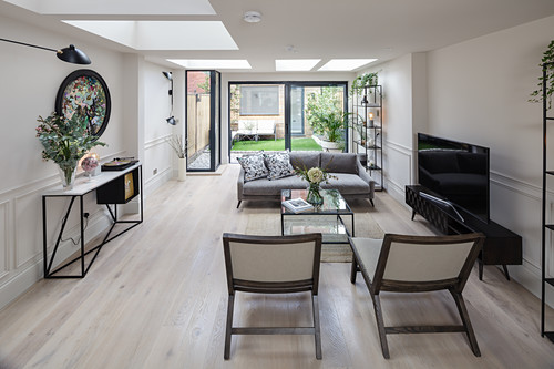 Elongated living room with skylights and glass wall overlooking garden