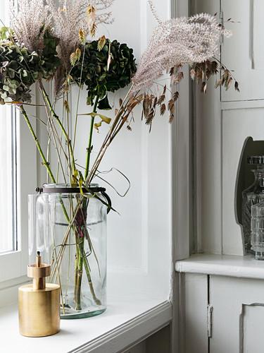 Dried flowers in vase on windowsill