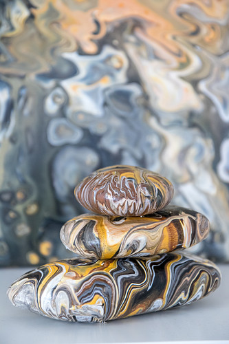 Stacked pebbles painted with marble pour technique in natural colours