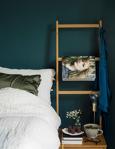 Weiss bezogenes Bett vor taubenblauer Wand mit Holzleiter und Modezeitschrift
