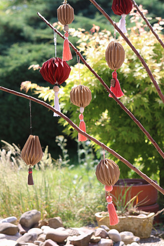 Handmade brown paper pendants with tassels as decorations for garden party