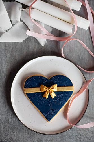 Large heart-shaped biscuit with blue fondant icing and golden bow