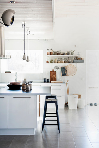 The industrial metal and wood kitchen stools echo the materials and structure used in the bookshelves along one wall of this kitchen