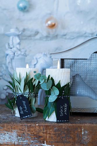 Kerzen mit Eukalyptuszweigen, Oliven- und Lorbeerbblättern und Widmung
