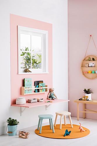 Schreibtisch unterm Fenster mit rosafarbenen Rahmen im Kinderzimmer