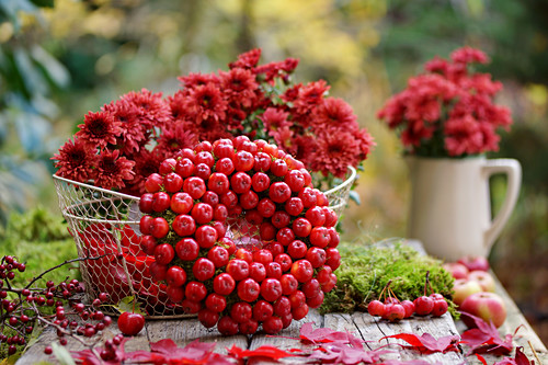 Kranz aus Zieräpfeln und Korb mit Chrysanthemen