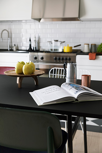 Open book on black dining table in kitchen