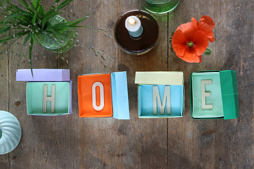 The word 'Home' made from letters in small boxes made from coloured paper