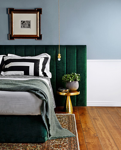 Double bed with headboard upholstered in green fabric