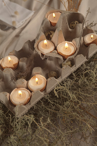 Arrangement of candles in egg shells in egg box