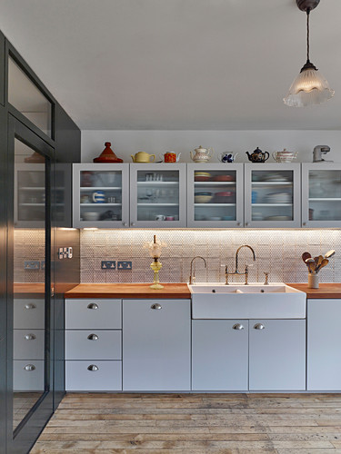 Classic kitchen in white with glass-fronted wall units and stoneware sink