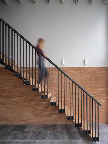 Frau in Bewegungsunschärfe geht freitragende Treppe hinunter