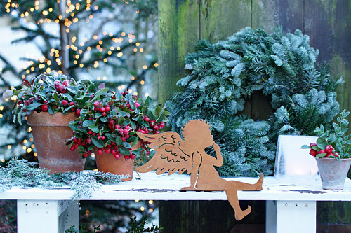 Metal angle, teaberry and wreath on table outside