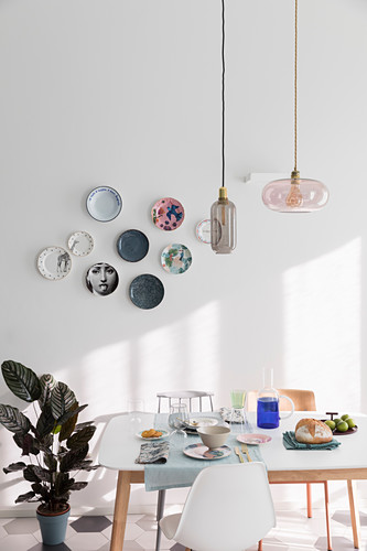 Plates decorating walls above set table in dining room